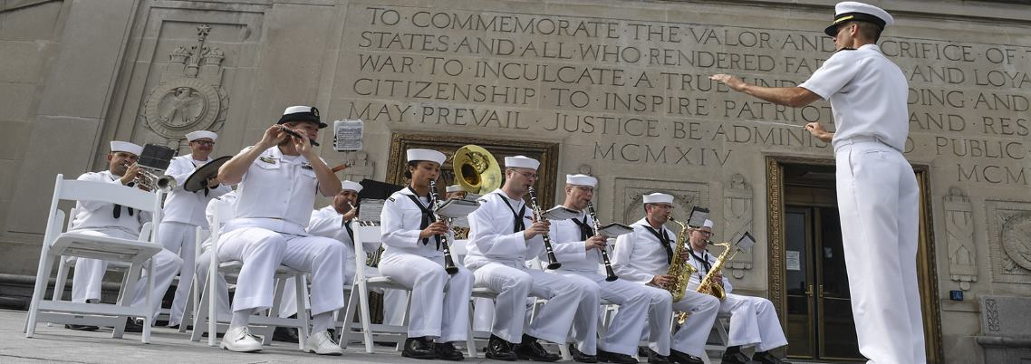 Image of Sailors playing instruments in front of a monument.